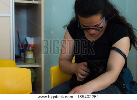 Eskisehir, Turkey - May 05, 2017: Woman Holding A Black Kitty In Her Arms In A Kindergarten Classroo
