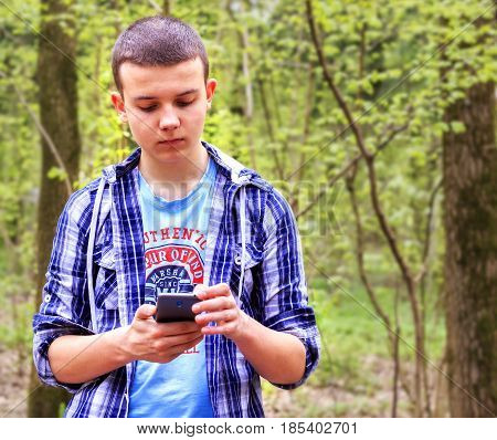 Young man stands in the woods thinks about something and works on the phone