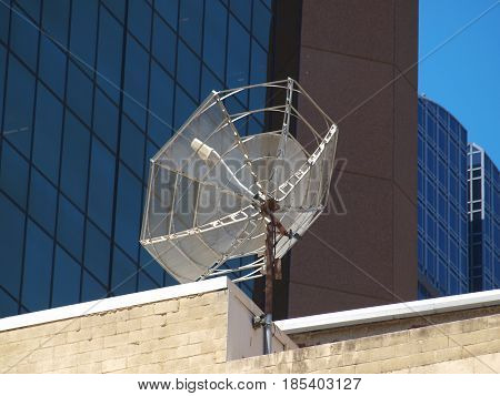 A satellite antenna sits high atop a building in the central business district. Two of the large churches in downtown broadcast live services on Sundays.