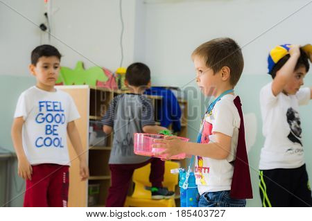 Eskisehir, Turkey - May 05, 2017: Sweet Little Boy With Red Cloak Carrying A Cup In Kindergarten Cla