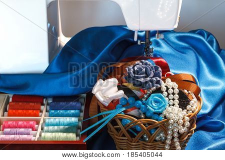 Sewing accessories colorful thread spools blue silk fabric decorations and sewing machine