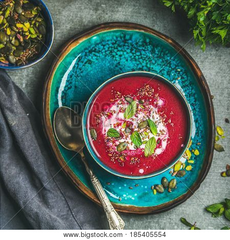 Spring detox beetroot soup with mint, chia, flax and pumpkin seeds on bright blue ceramic plate over grey concrete background, top view, square crop. Clean eating, weight loss, vegetarian food concept