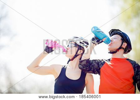 Bicyclists drink water from bottle