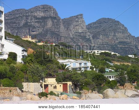 CLIFTON, CAPE TOWN SOUTH AFRICA, LANDSCAPE, HOUSES AND VEGETATION IN THE FORE GROUND AND A  MOUNTAIN IN THE BACK GROUND
