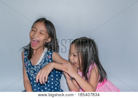 Beautiful Little Child And Her Sister Are Playing And Joyful On Gray Background. Concept Happiness A