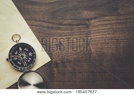traveling compass and old paper with copy space. traveling concept on the brown wooden table. traveling background. traveling directions.