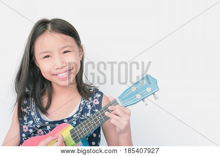 Selective Focus Beautiful Little Girl Smiling With Confidence And Playing Ukulele On White Backgroun