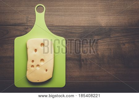 big pieces of cheese over cutting board on wooden table