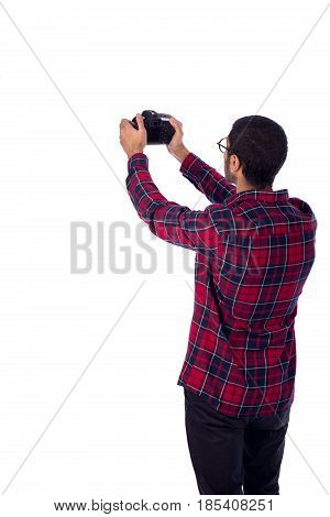 Happy friendly young photographer taking a photo guy wearing red caro shirt and jeans isolated on white background