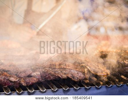 Grilling red meat and sausages at sunset outdoors gathering with friends and family poster