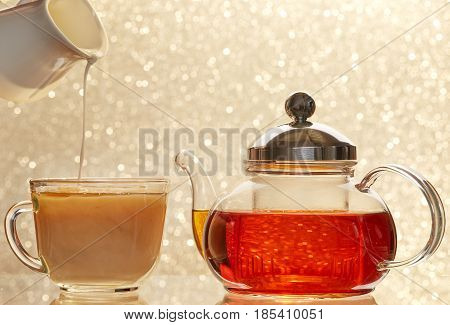 Dissolve milk in a cup of black tea. Transparent teapot and cup on blur background