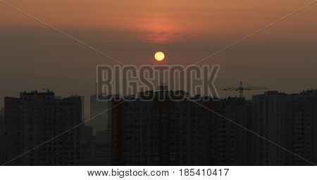 City sunset with a Sun disc in the middle of a red sky with appartment houses