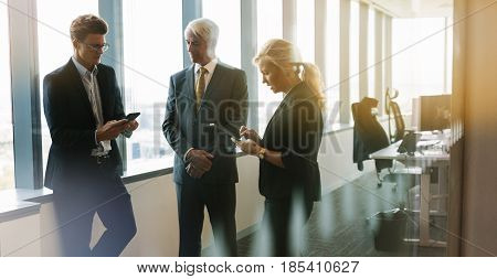 Three business people standing together in office with mobile phone and digital tablet. Corporate professional having informal meeting in modern office.