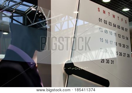 Male mannequin in a business suit behind a glass showcase with a clock and calendar for the month of May