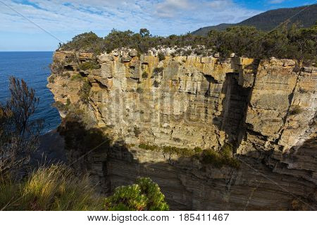 Tourist attraction named Devil'?s Kitchen, former sea cave now a deep narrow gulch, geological formations torn by sea waves, wind over millions of years at Tasman National Park, Tasmania, Australia