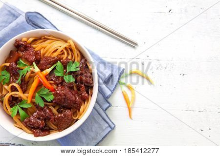 Thai noodles with beef and hot red chili pepper and space for copy