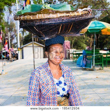 MINGUN MYANMAR -MARC 6, 2017: Woman wears on his head baskets of green banana leaves in Mingun on March 6, 2017, Myanmar. (Burma)