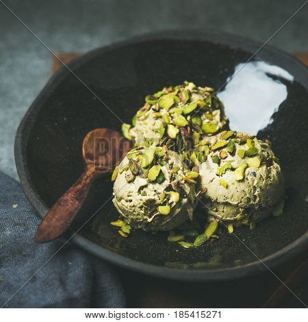 Homemade pistachio ice cream scoops with crashed pistachio nuts in dark plate over wooden board, selective focus, square crop