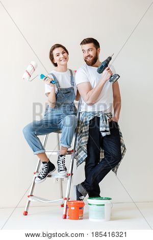 Picture of young happy loving couple sitting indoors in new flat and make repair.
