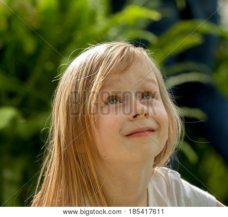 portrait, little girl seven years old, in a botanical garden, looking up, long blond wheaten hair, white tank top, cute, nice-looking