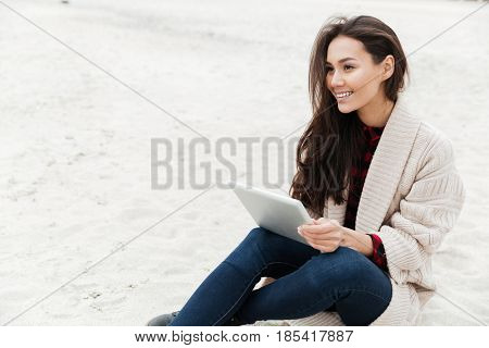 Image of pretty young caucasian lady walking outdoors at beach wearing warm jacket using tablet computer. Looking aside.