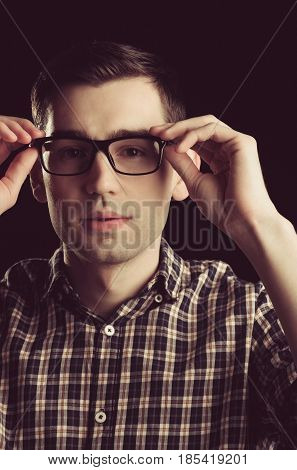 student. young guy nerd in glasses and fashionable checkered shirt has stylish hair isolated on black background