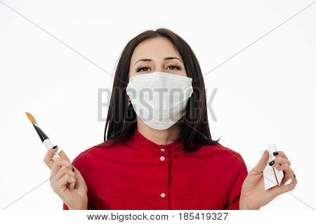 Pretty girl visagiste or adorable woman in medical face mask with brunette hair with cream tubes makeup foundation and brush in hands in red shirt isolated on white. Healthy cosmetic and skincare