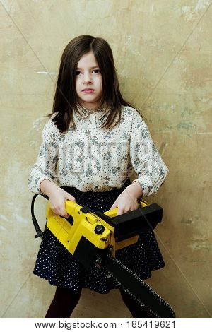 Cute small little girl child builder with long brunette hair holding portable electric power yellow color saw or chainsaw cutting tool on beige wall. Danger and risk