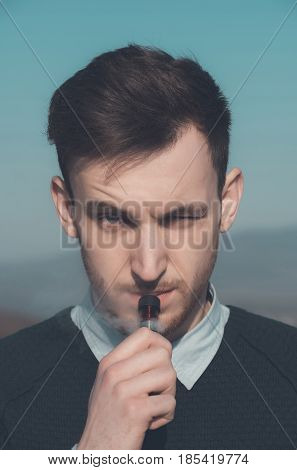 Unshaven handsome young man smoking or vaping electronic cigarette with vapor cloud and squinting eyes on sunny summer day outdoors on blue sky background. Health safety and addiction