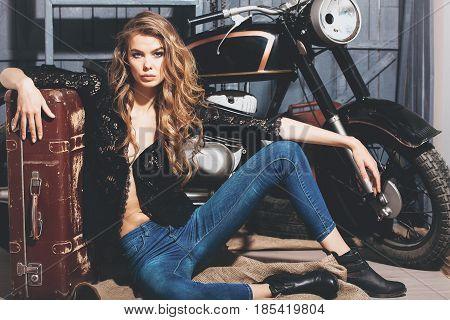 Pretty Girl Biker In Erotic Shirt And Jeans On Floor
