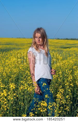 Beautiful Young Woman, Blonde Poses In A Field Of Yellow Flowers