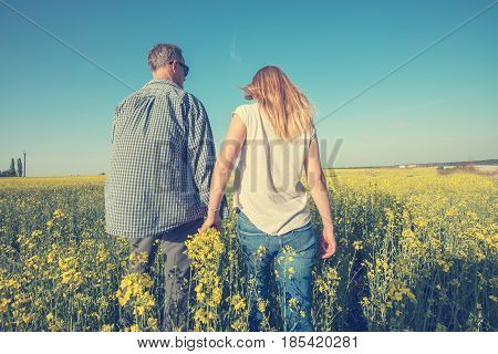 Man With A Young Woman Are Walking Through A Field Of Yellow Flowers