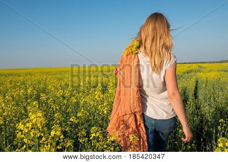 Young Woman, Blonde With Orange Scarf Is Walking Through A Field