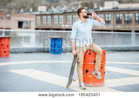 Handsome businessman having a coffeebreak sitting with skateboard on the rooftop on the industrial background
