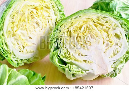 section of young fresh gren head of cabbage cutted in two parts against wooden background