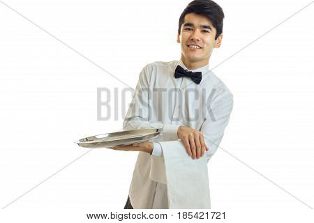 perky young waiter in a white shirt with black bow tie holding a towel and tray for dishware isolated on white background