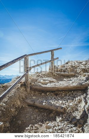 Stairs on an alpine trekking route seemingly leading to the heavens with vivid blue skies.