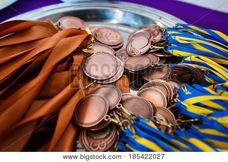 Many bronze medals with copper ribbons and yellow- blue ribbons on a silver tray Champions awards achievements in sport the third place prize for the winner