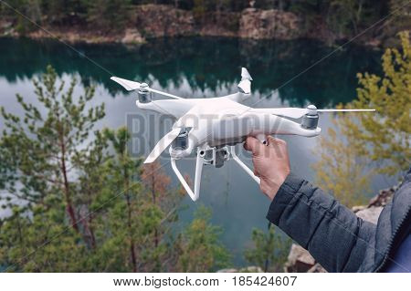 The man in dark pants and a jacket holding quadrocopter in his hands before takeoff on the background of a forest lake. Unmanned aerial copter. Aeromodelling, hobby, leisure concept