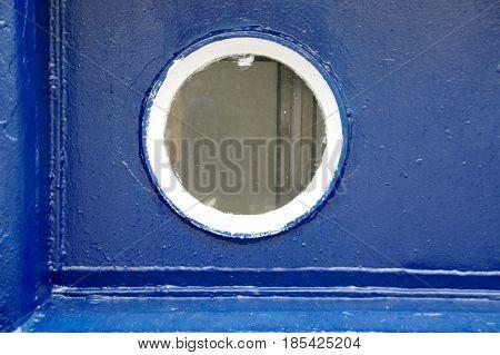 The old ship porthole on dark blue background