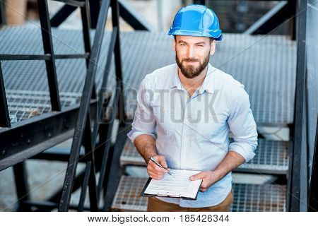 Handsome foreman or builder in helmet supervising structure standing on the new building stairs