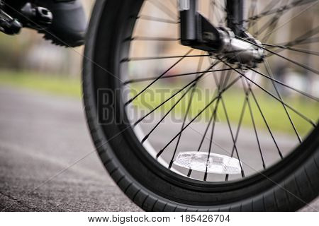 Closeup of a foot on pedal and bike wheel riding at the school's track. No motion blur is used to convey movement. No sunsets.