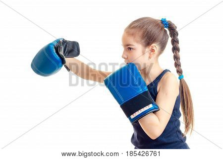 little baby-girl with a pigtail stands sideways in front of the camera and stretched forward hand in big boxing gloves isolated on white background