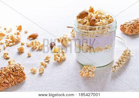 greek yogurt with fruit crunchy muesli bars wheat cones linen background healthy breakfast concept
