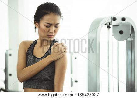 Asian woman in sportswear having shoulder pain at the gym.