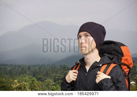 Young man with backpack standing against a mountain landscape.