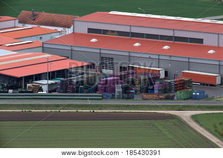 Industrial Plant With Containers, Freight Trucks And Pallets