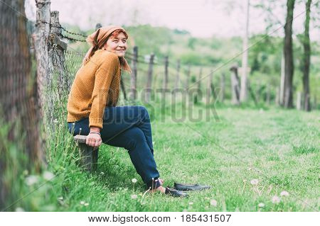 Peasant mature woman sitting on the bench resting