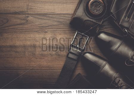 brown shoes, socks, belt, and film camera on wooden background. men's accessories on the table. above view on men's accessories. brown leather men's accessories. men's accessories concept.