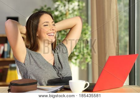 Satisfied student resting with hands on head sitting in a chair looking through a window in the living room at home